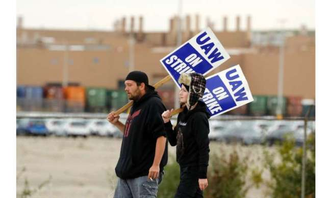 Workers walk the picket line outside General Motors Orion Assembly on October 11 in Orion Township, Michigan