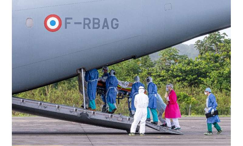 Medical staff carry a patient infected with Covid-19 into an Airbus A400M at an air-base in Matoury, Guiana