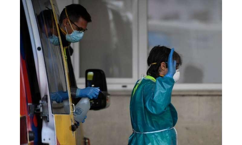 Healthcare workers disinfect their protective gear at a hospital in Madrid in Spain, one of the worst-hit countries