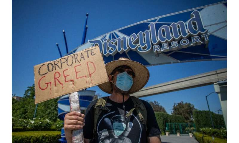A man holds a sign in front of Disneyland Resort calling for higher safety standards before its reopening  amid the coronavirus