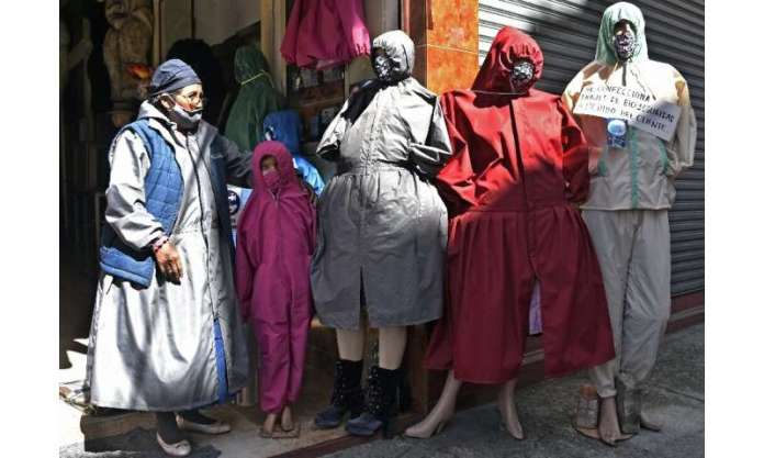 """A woman stands next to protective suits designed for """"cholitas"""" (indigenous women who wear typical skirts) outside a s"""