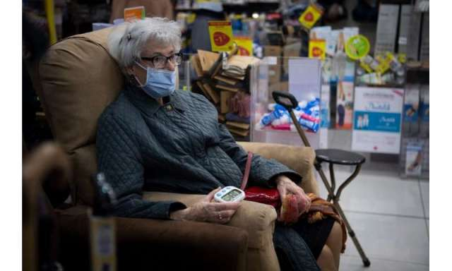 An elderly woman waits after being vaccinated with the AstraZeneca/Oxford Covid-19 vaccine, in a pharmacy in Nantes in western F
