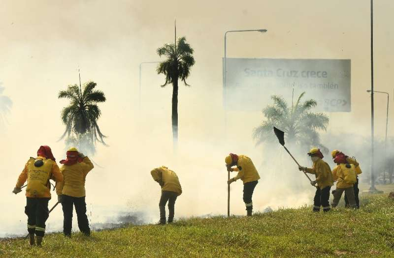 Firefighters try to extinguish a grass fire near the Viru Viru airport in Santa Cruz, Bolivia on August 1, 2021; the department