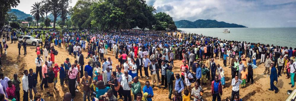 Hundreds of people awaiting baptism in blue and white robes at Lake Kivu in Rwanda.