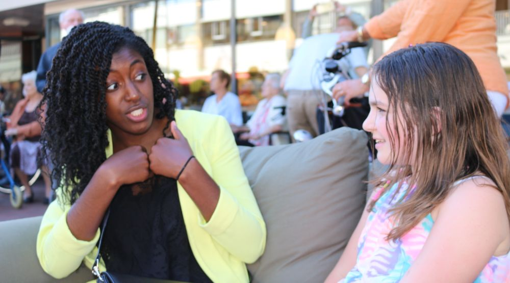 Jenny Simpeh, 21, from Rotterdam, speaking with a girl on the Sabbath sofa. (Chigemezi N. Wogu)
