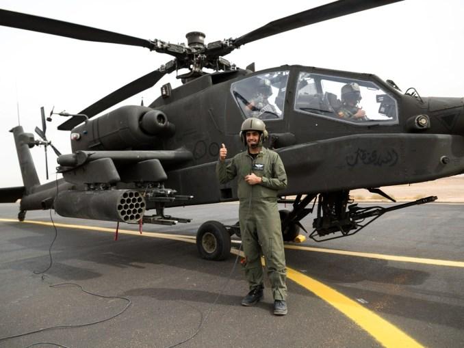 فرد من القوات البرية الملكية السعودية من الكتيبة الأولى، مجموعة الطيران الثالثة، إلى جانب مروحية أباتشي قبل هجوم جوي عملي مع لواء الطيران القتالي 42 أثناء تمرين عسكري في 14 نيسان 2014 بالقرب من تبوك، المملكة العربية السعودية