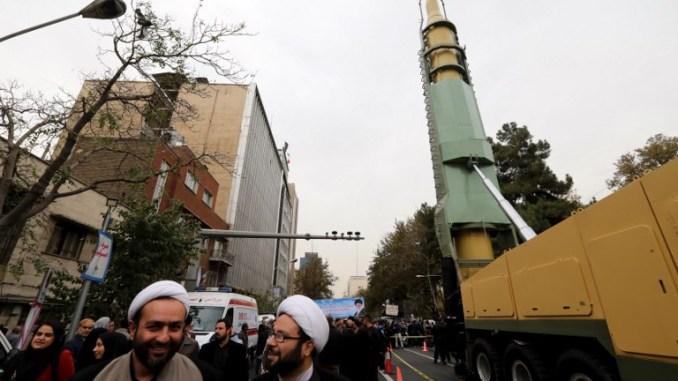 """إيرانيون يجتمعون بجانب نسخة طبق الأصل من صاروخ """"غدر"""" (Ghadr) البالستي متوسط المدى خلال مظاهرة خارج السفارة الأميركية السابقة في العاصمة الإيرانية طهران في 4 نوفمبر 2017 (AFP)"""