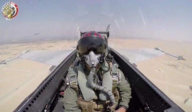 صورة مأخوذة من شريط فيديو نشرته وزارة الدفاع المصرية في 25 تشرين الثاني/نوفمبر 2017 تُظهر طيار من سلاح الجو المصري يجلس في قمرة القيادة، ويُحلّق فوق الصحراء (AFP)