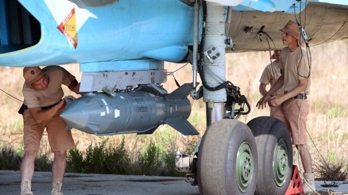 """صورة تم التقاطها في 3 تشرين الأول/أكتوبر 2015 تُظهر فنيّين في سلاح الجو الروسي يفحصون طائرة مقاتلة روسية من طراز """"سو-34"""" في قاعدة حميميم الجوية في محافظة اللاذقية السورية (AFP)"""
