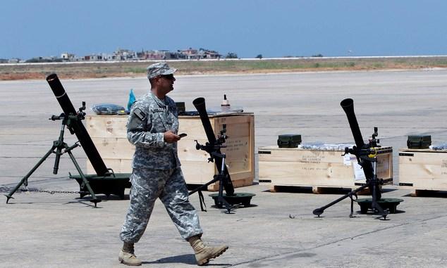 جندي أميركي يسير أمام قذائف هاون تابعة بالجيش اللبناني ضمن الهبة العسكرية الأميركية في مطار رفيق الحريري الدولي في بيروت في 29 آب/أغسطس 2014 (AP/Bilal Hussein)