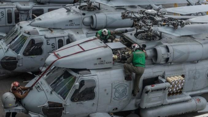 """صورة خاصة بالبحرية الأميركية تُظهر بحارة أميركيين وهم يتفقدون مروحيات سيهوك أم أتش 60 آر من على متن حاملة الطائرات """"يو أس أس رونالد ريغان"""" في 18 أيار/مايو 2017 في مياه جنوب اليابان (AFP)"""