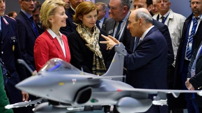 وزيرة الدفاع الألمانية أورسولا فون دير لين (إلى اليسار) ونظيرتها الفرنسية فلورنس بارلي (إلى اليمين) تستمعان إلى الرئيس التنفيذي لشركة داسو للطيران إريك ترابييه خلف نموذج لطائرة مقاتلة رافال في معرض برلين الدولي للطيران في 26 نيسان/أبريل 2018 (AFP)