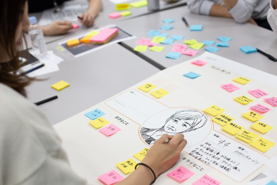 A woman drawing a persona on a canvas created during a design sprint workshop.