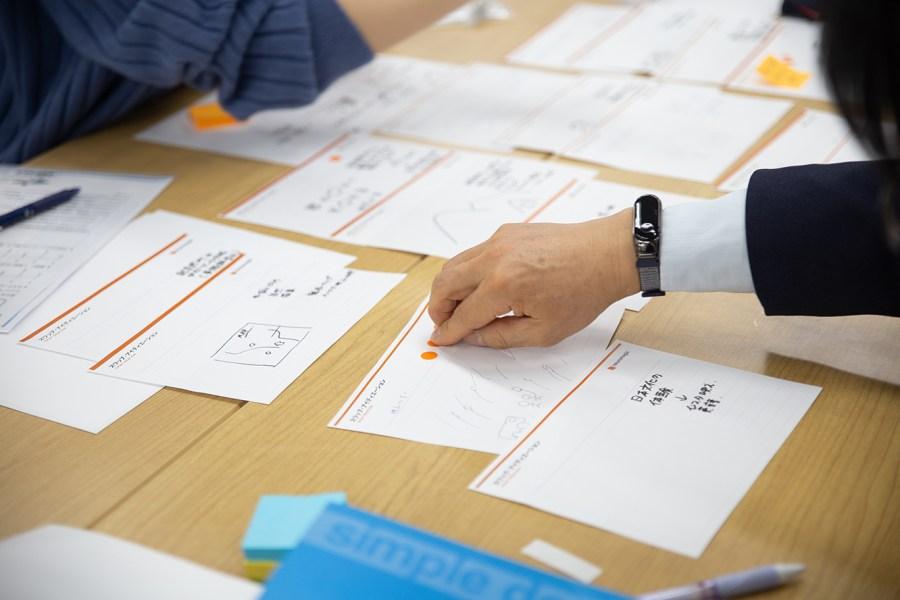 デザインスプリントワークショップでドット投票をする男性