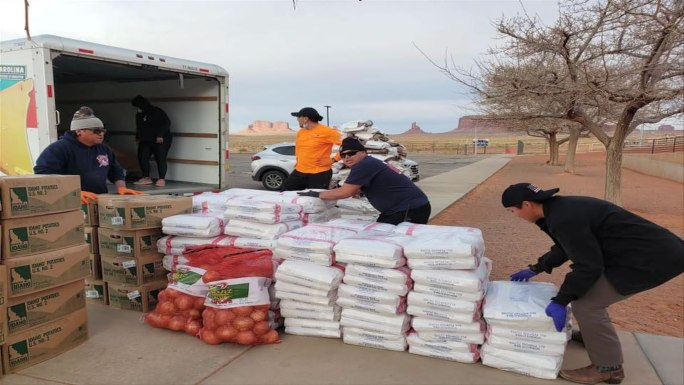 Loading bags of food and supplies in a truck for Navajo Hopi COVID-19 relief efforts