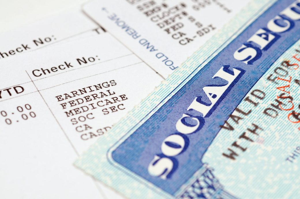 Social Security card and check stub showing tax withholdings