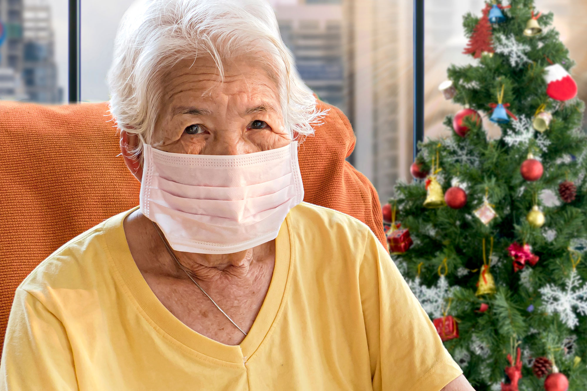 an older woman wearing a mask sits alone next to a Christmas tree