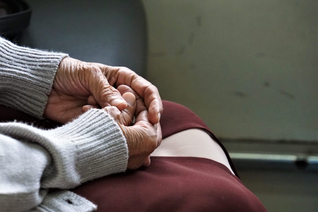 close up of an older women with her hands in her lap