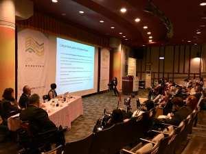 論壇發表講者郭慧瑜身著黑衣坐在大螢幕前報告研究,可見講堂一排排觀眾與其使用的行動輔具。三位發表人與主持人坐在照片的左側角落