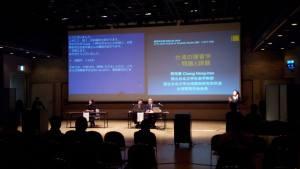 照片中分講者坐在投影片的大螢幕前演講的現場,可見講者身旁坐著日籍翻譯,旁邊也站了手語翻譯員。大螢幕投影片顯示講題為台灣障礙研究學的經驗。照片可見黑壓壓的聽眾背影