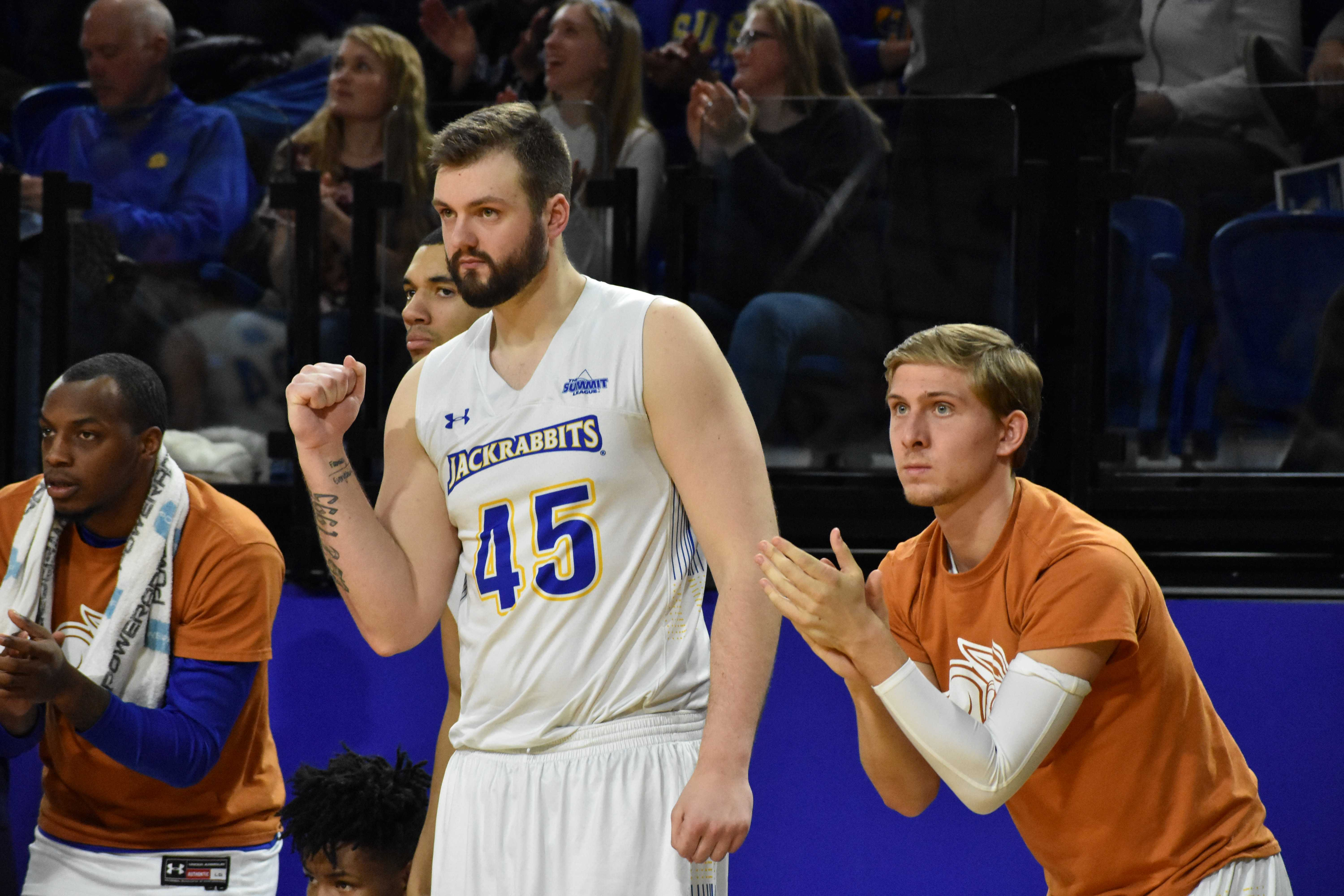 ABBY FULLENKAMP Senior forward Ian Theisen (45) and sophomore guard Beau Brown (15) cheer on their teammates during the second half of the game against USD Feb. 22. The Jacks won 76-72. The men are the first seed for the Summit League Tournament.