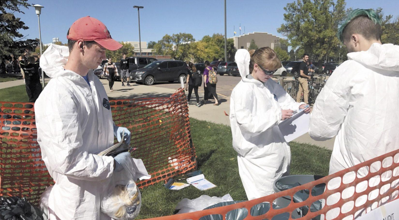 MACKENZIE HUBER Sustainability Specialist Jennifer McLaughlin, Sustainability Council President Kory Heier and Dylan Lewark, freshman computer science major, sort trash for a waste audit in front of The Union Sept. 20.
