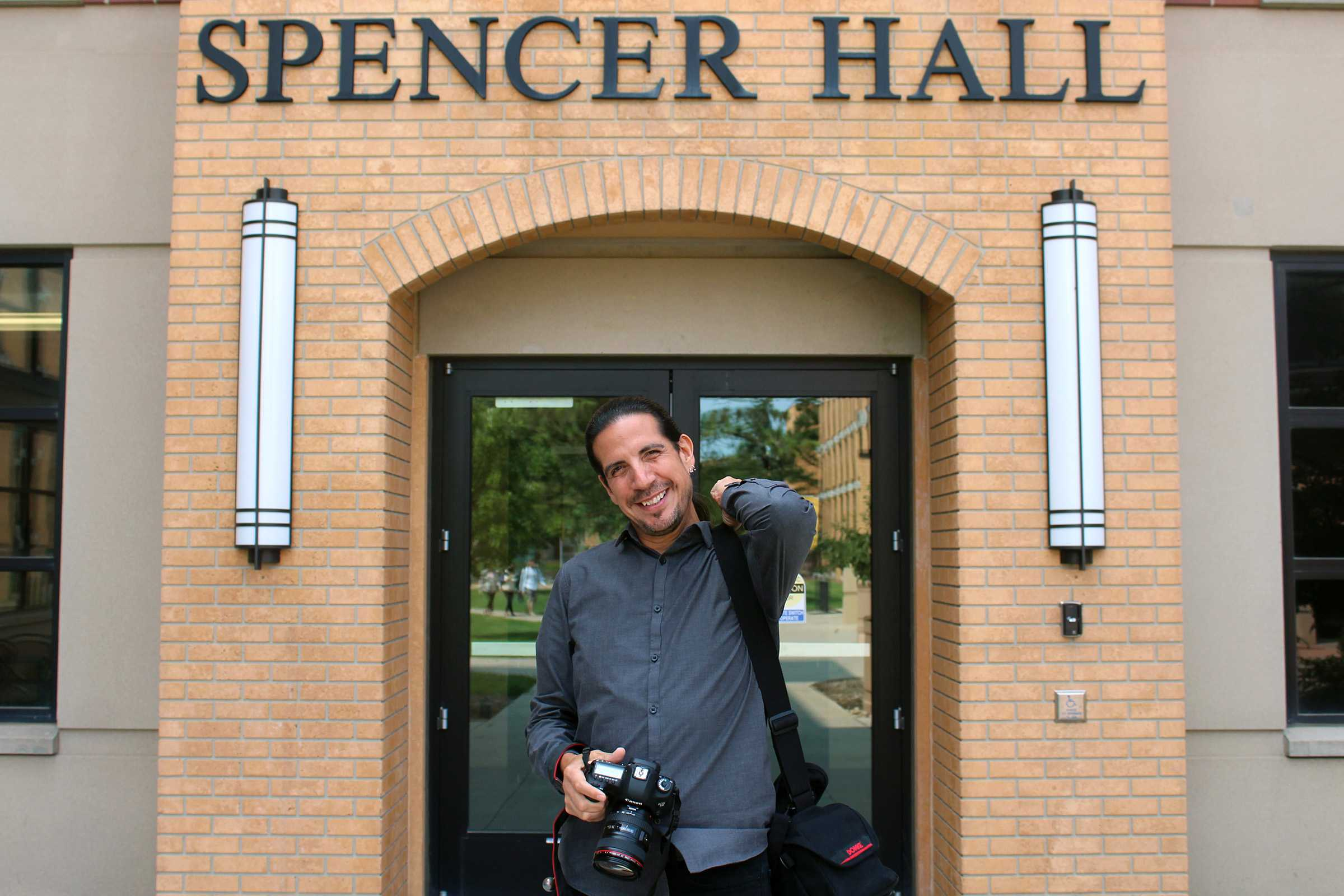 MIRANDA SAMPSON Frank Robertson, instructor at the School of Communication and Journalism, poses in front of Spencer Hall which is named after his late mother, Velva Lu Spencer, who was the Native American student adviser during her time on campus.