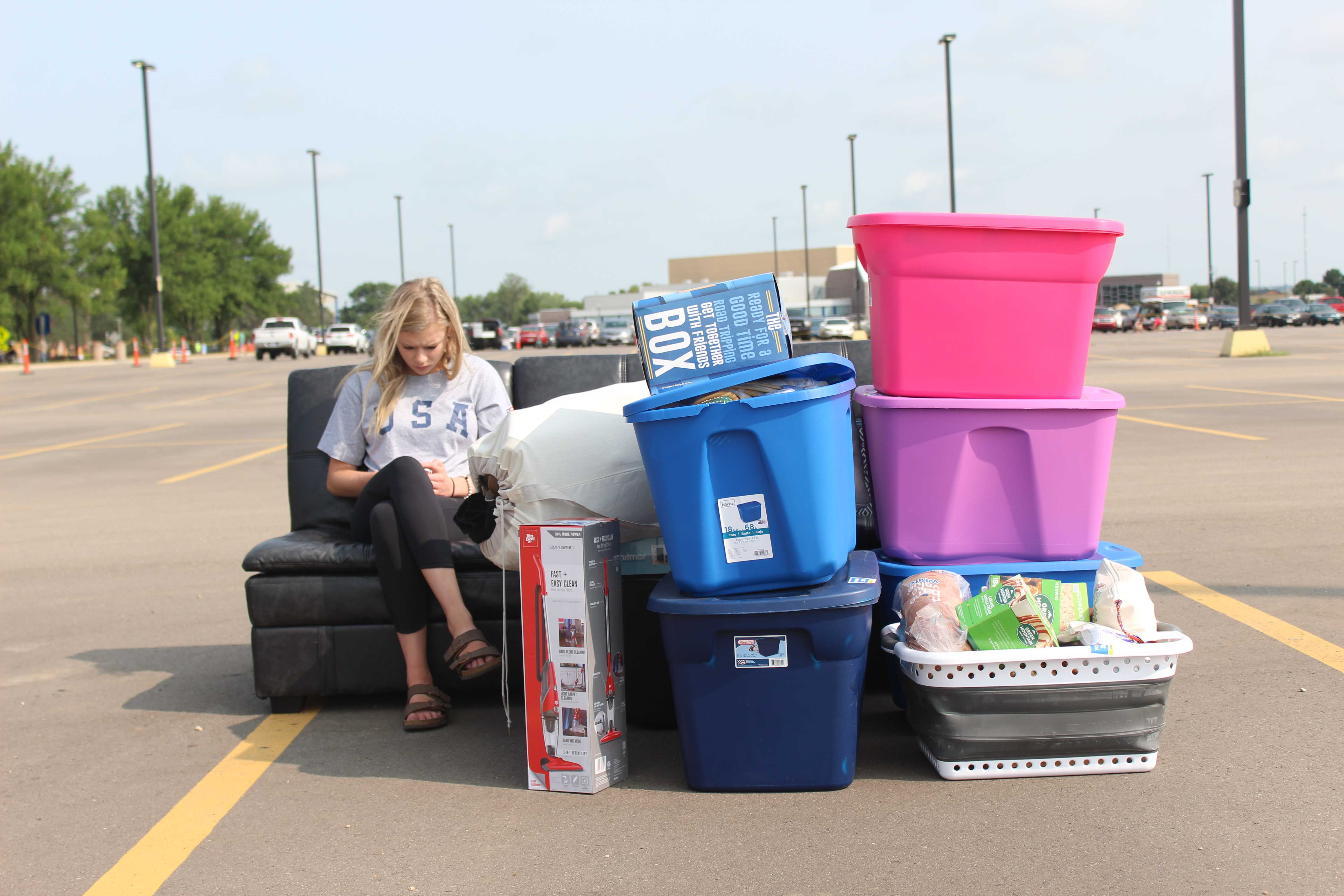 A SDSU sophomore sits with her sisters' stuff in the parking lot while her sister and parents mover her stuff in her resident hall during Meet State Friday, Aug. 18, 2018 at South Dakota State University.