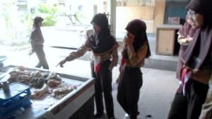 Seorang siswa SD Ta'mirul Islam Surakarta penasaran dengan jenis barang dagangan di Pasar Penumping.