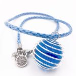 A necklace with a round blue jewel is wrapped up in thin silver metal on a blue cord.