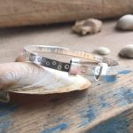 A silver bracelet perched on an oyster shell.