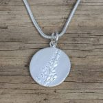 A silver disk on a silver chain necklace