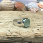 A chunky silver ring with a green seaglass stone.