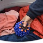 A hand placing a Cora Ball into a washing machine.