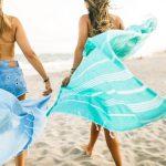Shop: Two women walking along a beach each with a devocean tie-dyed beach blanket
