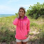 Shop: A woman wearing a Devocean hoodie in bright pink.
