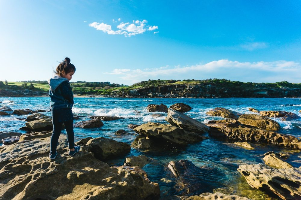 Young girl looking in rock pools