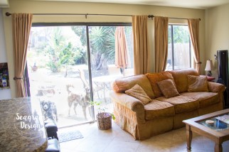 A small, cozy family room with an orange couch, tan walls, and tan curtains.