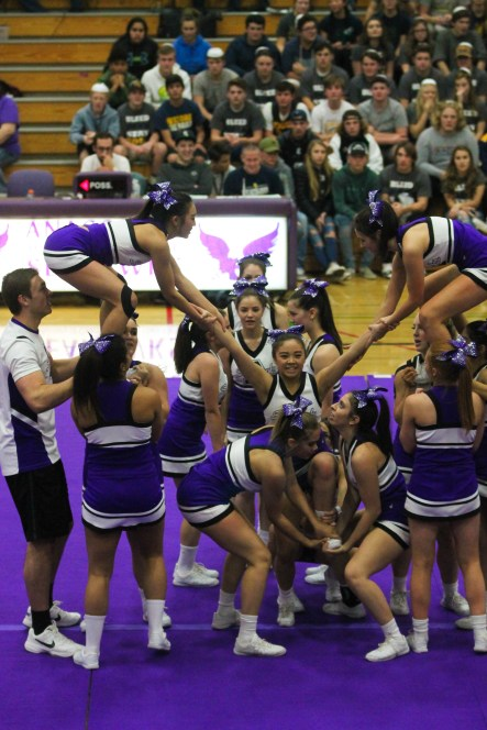 The cheer squad prepares to stunt Serena Rivas during their half time routine.