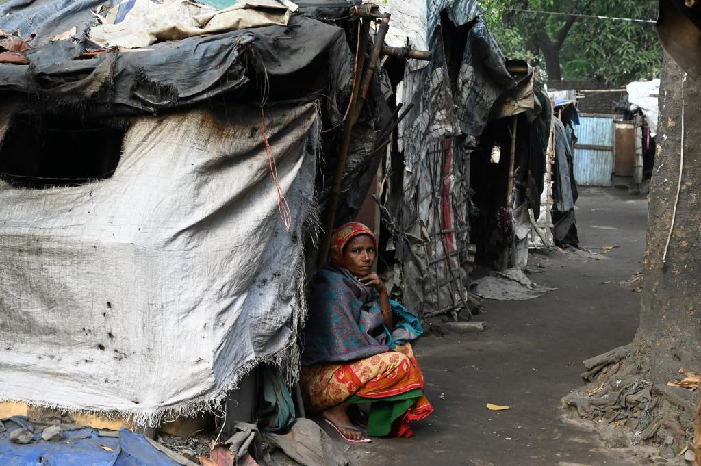 Image of woman looking at camera in what appears to be a makeshift home or shelter.