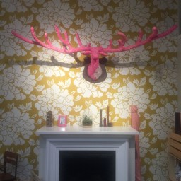 Back wall of Fancy Tiger Craft store adorned with white and yellow wallpaper and pink wooden deer bust