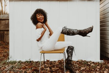 African American model kicks leg up and laughs while sitting on yellow mid century modern chair