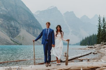 Bride and groom standing with canoe paddles at their Moraine Lake Wedding