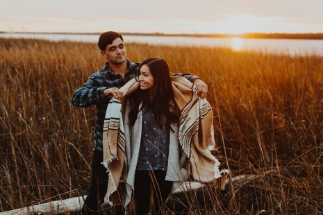 Rugged couple embracing at sunset on the Oregon Coast during their engagement shoot