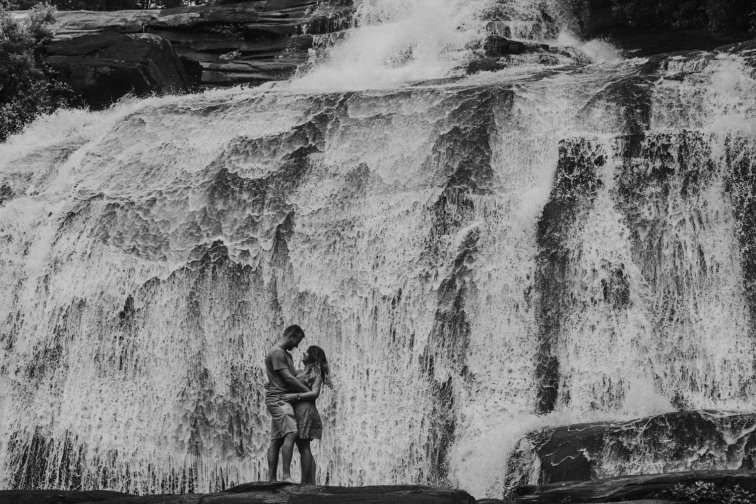 Couple stands facing each other in front of waterfall during their oregon engagement photos