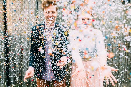 Couple throws confetti during their fun and bright engagement session