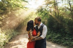 Sunsets through the forest mist over tattooed couple wearing a suit and red dress