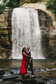 woman in red dress with fiancé embrace each other among the forest of Asheville during their engagement session