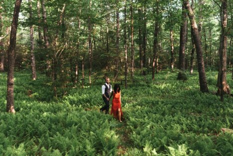 woman in red dress with finance walks among the forest of Asheville during their engagement session