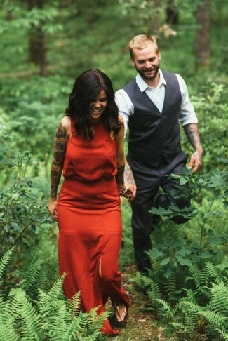 woman in red dress with fiance walks among the forest of Asheville during their engagement session